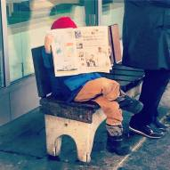 Ah, our perfect son, reading a French newspaper at the bus stop before school.